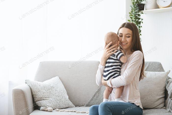 Mutter zärtlich halten ihr neugeborenes Baby beim Sitzen auf Sofa