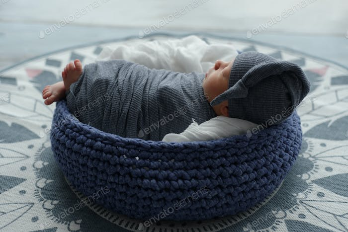 Newborn baby boy wrapped in gray fabric