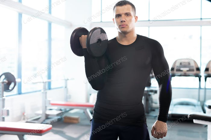 Handsome Fitness Instructor Posing with Dumbbell in Gym