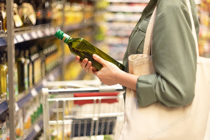 Girl choosing bottle of oil in grocery section of supermarket. Copy space. Healthy diet concept