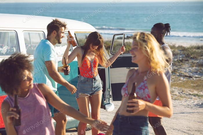 Front view of happy group of diverse friends dancing together near camper van at beach