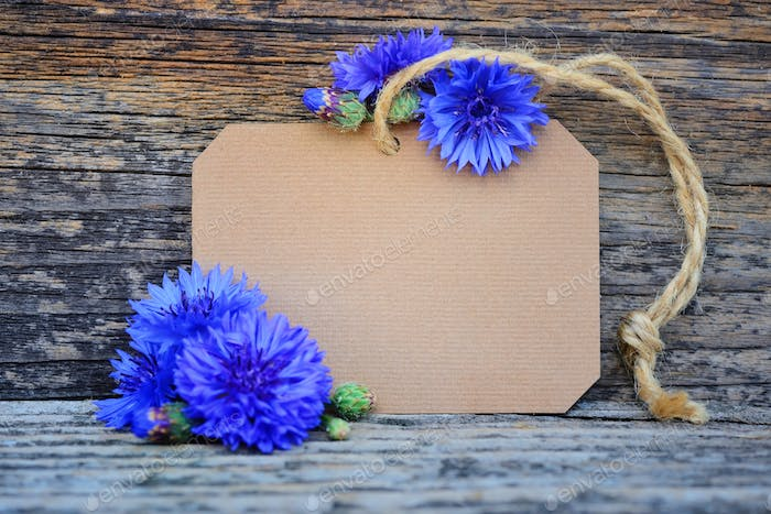 Paper tag with fresh cornflowers (Centaurea cyanus) on wooden ta