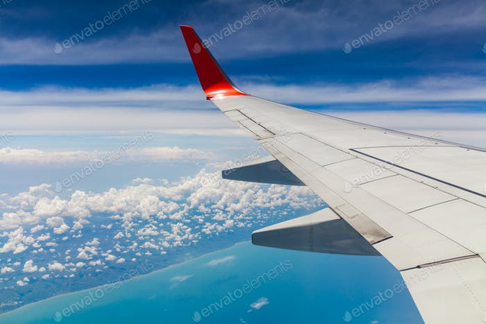 Aerial view of cloud blue sky and plane wing view through the airplane window