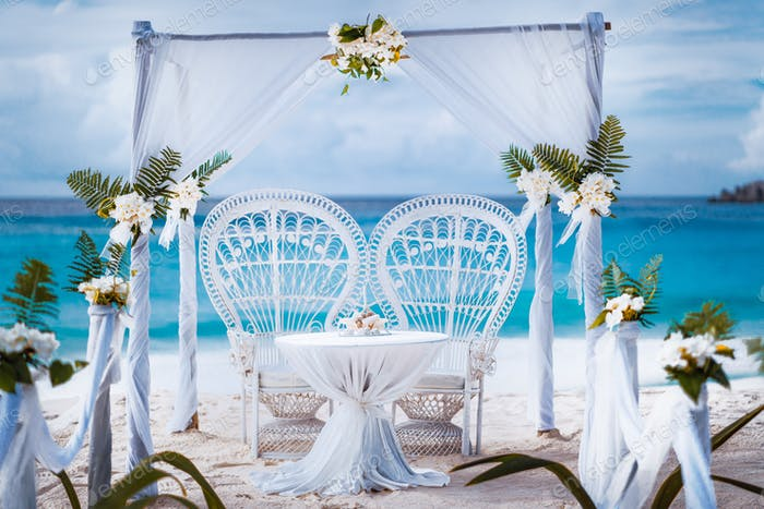 Beach wedding arch gazebo ceremonial decorated with white flowers on a tropical grand anse sand