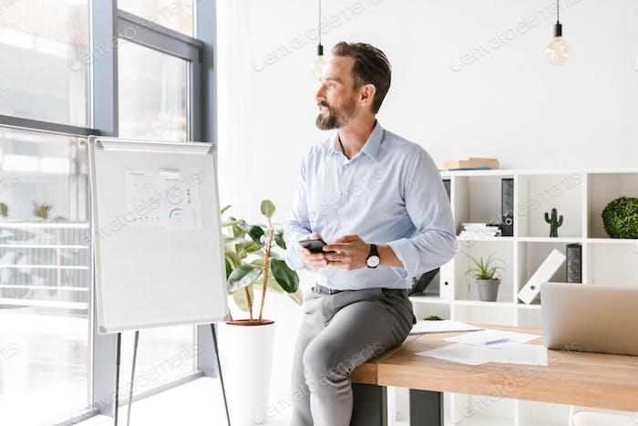 Confident businessman using mobile phone