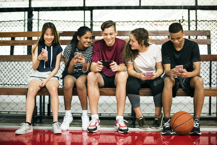Group of young teenager friends on a basketball court relaxing using smartphone