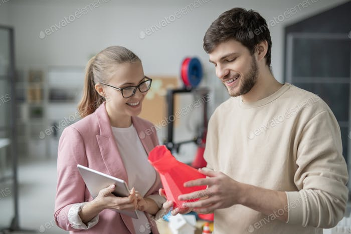 Happy young businessman showing red geometric object just printed in 3d printer
