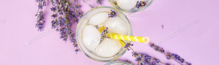 Banner with Lavender lemonade with lemon and ice on purple background.