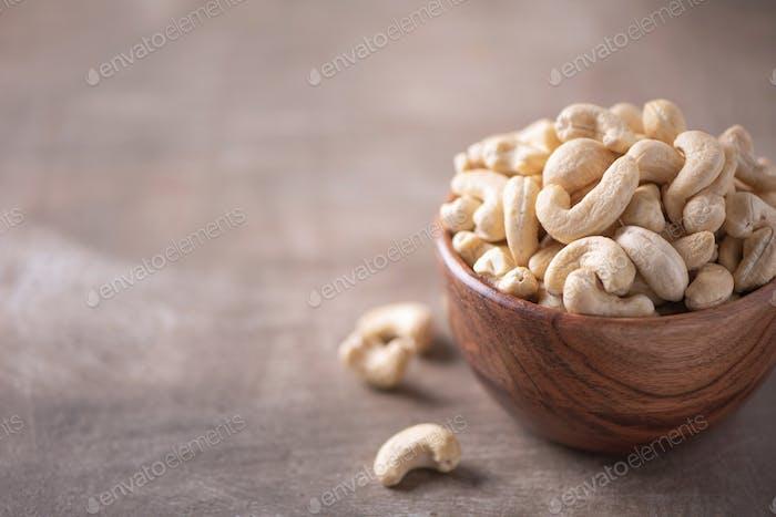 Cashew-Nüsse in Holzschale auf Holz strukturierten Hintergrund. Kopierraum. Superfood, vegan, vegetarisch