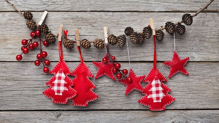 Christmas felt decorations hanging on stick with pine cones