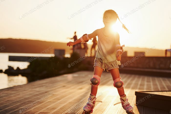 Happy cute kid riding on her roller skates. Unbelievable sunlight