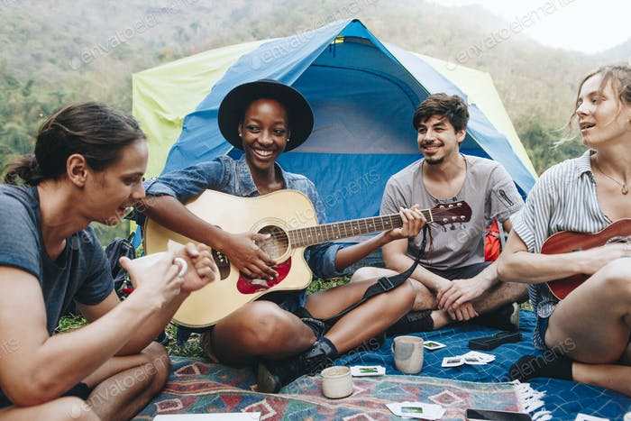 Group of young adult friends in campsite playing guitar