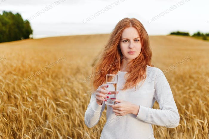 Young red-haired woman in field holding glass with drinking water
