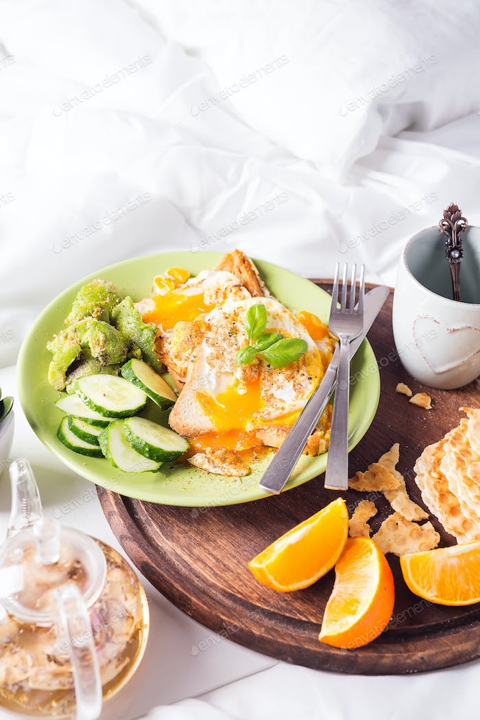 Breakfast eggs on a white plate with half avocado, cucumbers on a wooden plate on bed