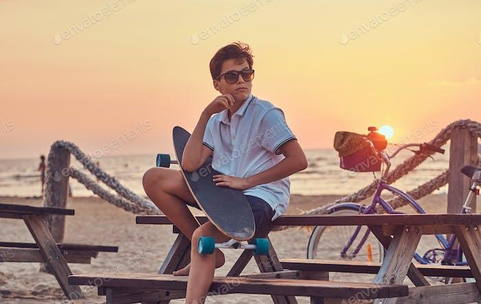 Junge Skater Junge sitzt auf einer Bank vor dem Hintergrund einer Seekoast am hellen Sonnenuntergang.