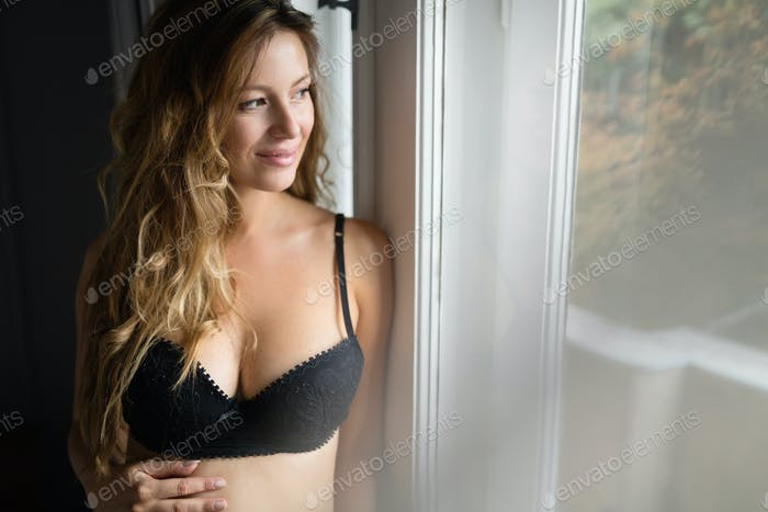 Closeup beautiful pregnant lady in elegant pose in black lingeri
