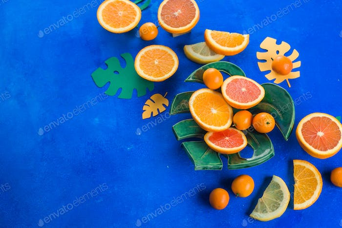 Mango, oranges, kumquat and other tropical fruits on a monstera plate. Bright blue background with