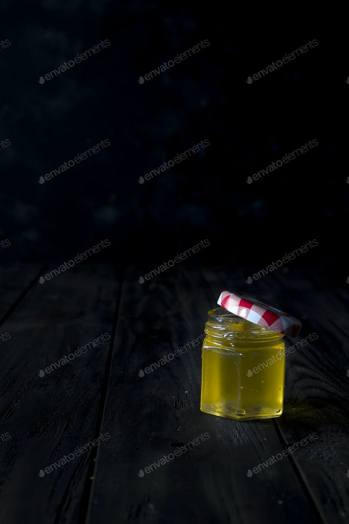Honey jar with a wooden stick drains honey on an dark background , pure natural sweet goodness.