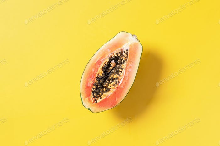 Halved papaya on yellow background. Top view. Copy space. Summer time. Tropical travel, exotic fruit