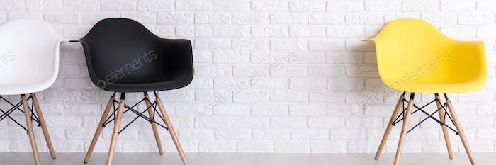 Brick wall and three armchairs