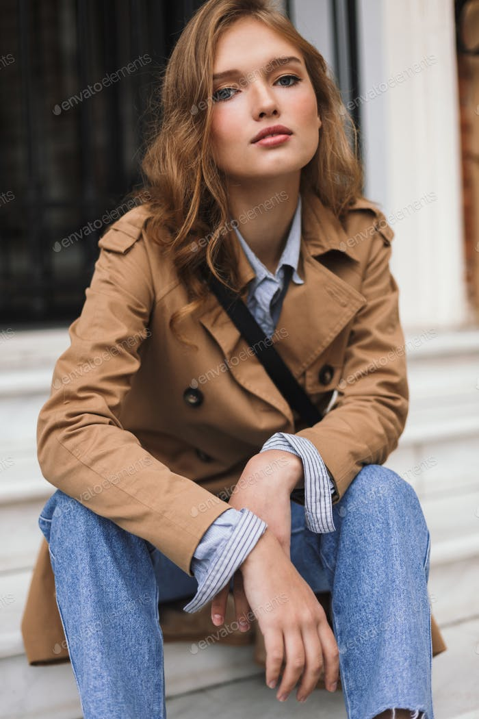 Nice girl in trench coat and jeans dreamily looking in camera si