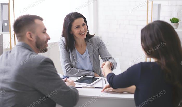 Positive Versicherungsmakler Handshaking mit jungen Paar