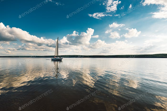 landscape. boat with a sail on the lake at sunset