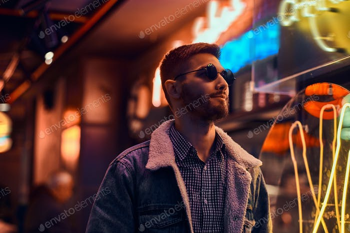 Handsome man standing in the night on the street. Illuminated signboards, neon, lights