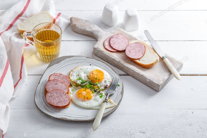 Fried eggs with sausage and toast on white background, breakfast