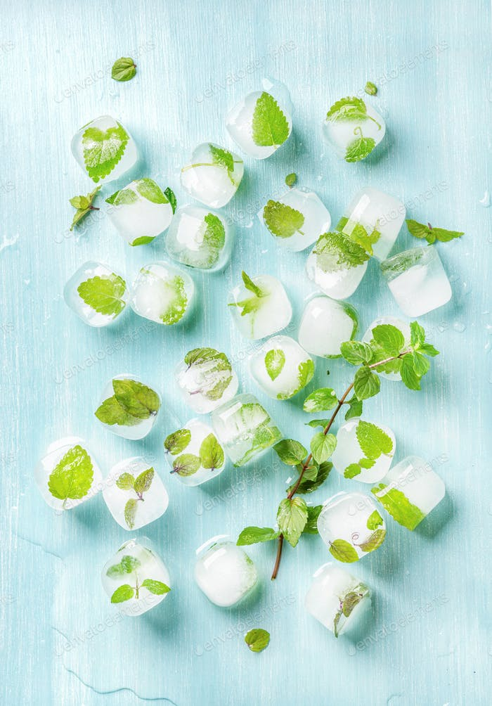 Ice cubes with frozen mint leaves inside on blue Turquoise background, top view