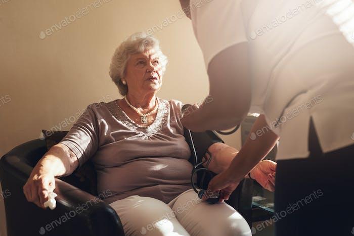Krankenschwester, die den Blutdruck ihres älteren Patienten messen