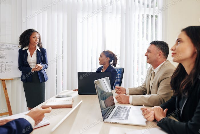 Business people listening to coworker at meeting