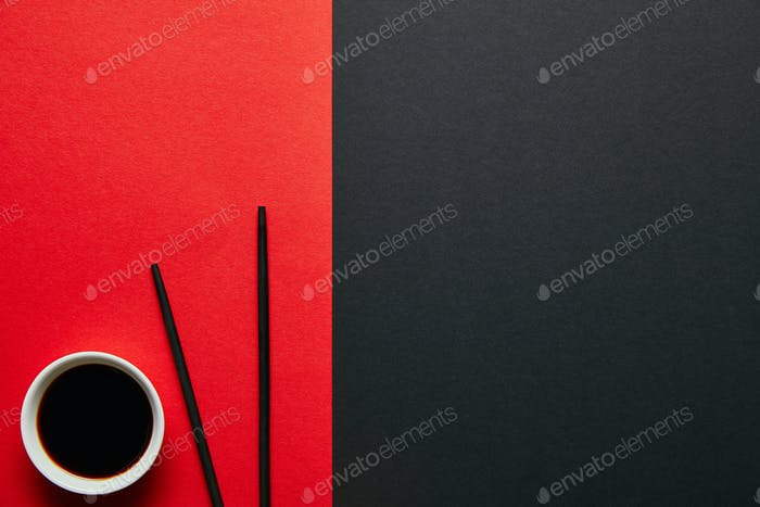 top view of soya sauce in bowl and chopsticks on red and black background