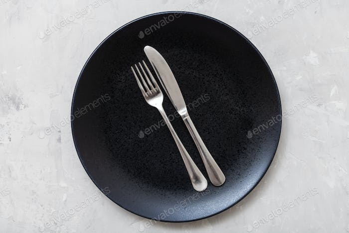 top view of black plate with flatware on concrete