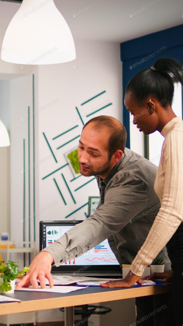 Разнообразные деловые люди, общающиеся в стартовом бизнес-офисе, стоя за столом