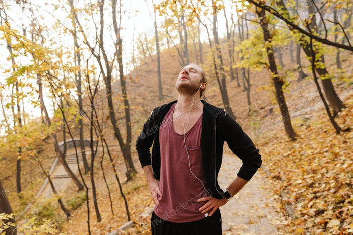 Attractive young fit sportsman jogging in the autumn forest