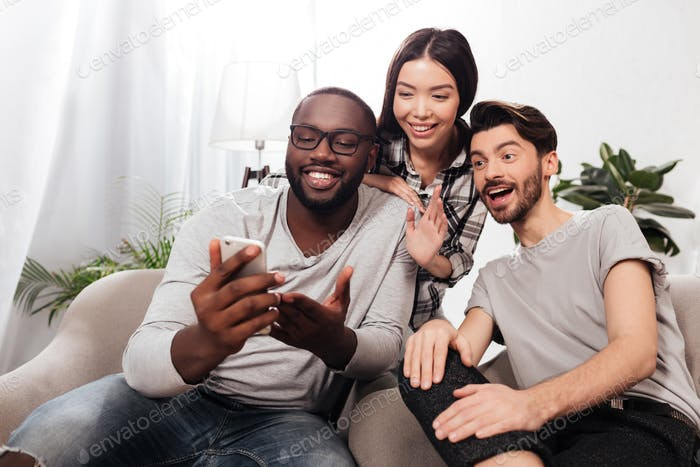 Portrait of three smiling friends sitting on sofa at home happily looking in mobile phone together