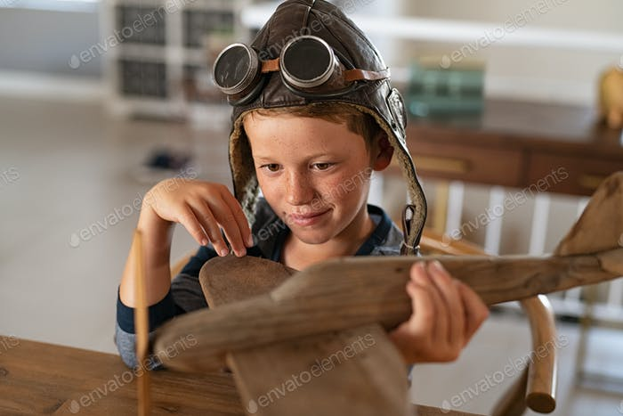 Child playing with wooden airplane at home