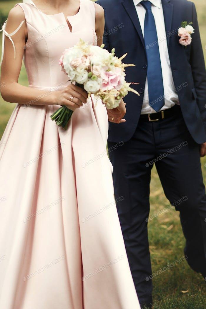 luxury happy wedding couple holding hands and walking