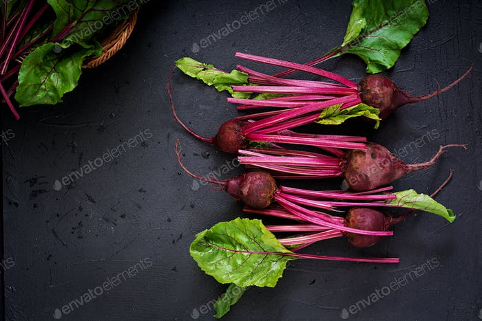 Young beetroot with a tops on a dark background. Flat lay. Top view.