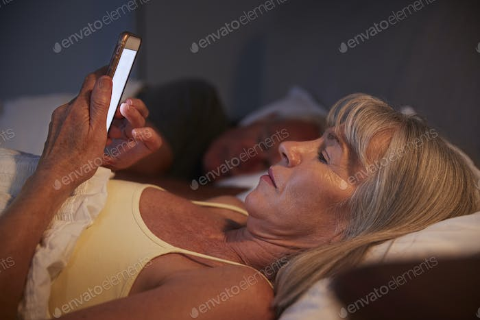 Sleepless Senior Woman In Bed At Night Using Mobile Phone