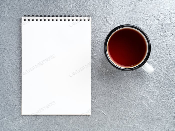 metal mug with tea, empty a blank sheet of Notepad on the spiral on a gray metallic background