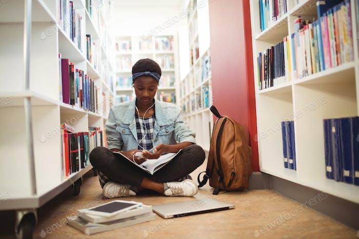 Schoolgirl listening music on headphones in library