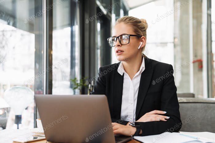 Mystery blonde business woman sitting by the table in cafe