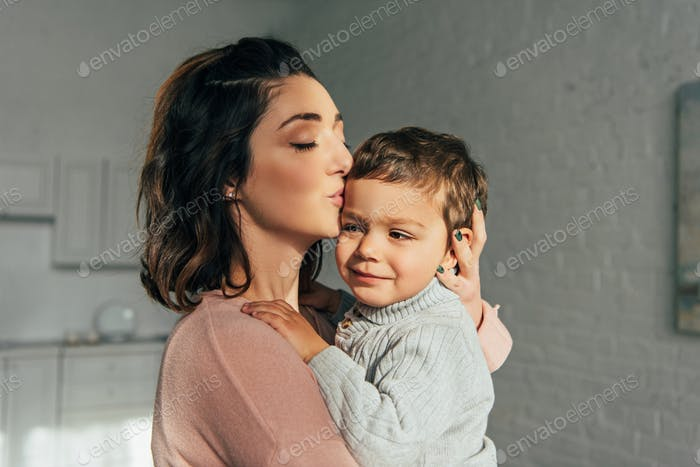 woman with closed eyes kissing and holding little son on hands