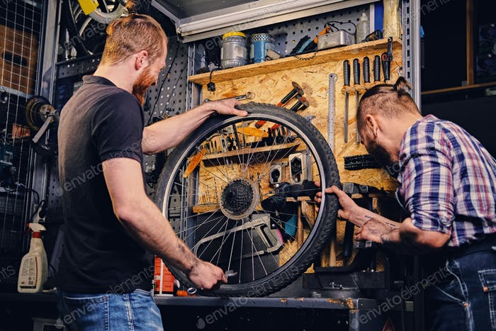 Bearded mechanics fixing bicycle's wheel in a workshop.