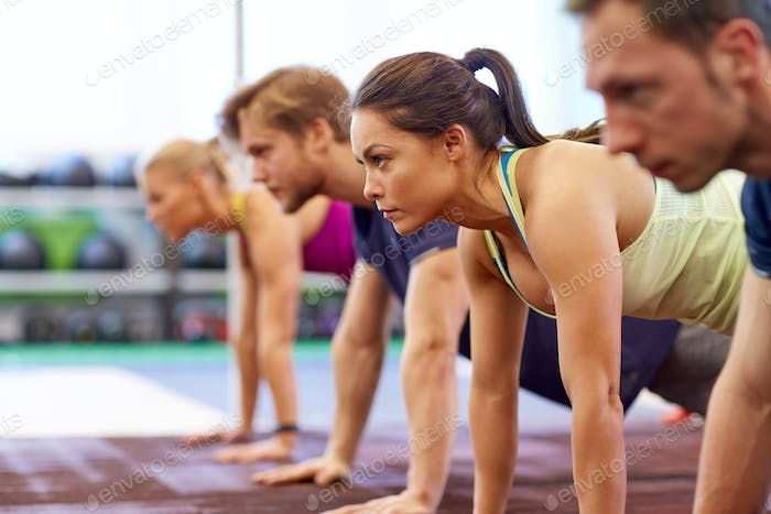 group of people doing straight arm plank in gym