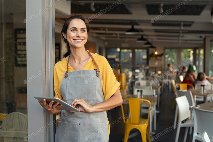 Successful owner standing at cafe entrance
