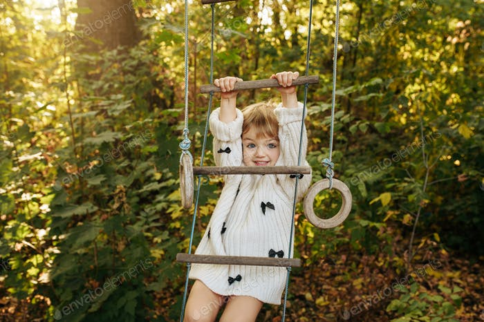 Little girl climbs by rope ladder in the garden