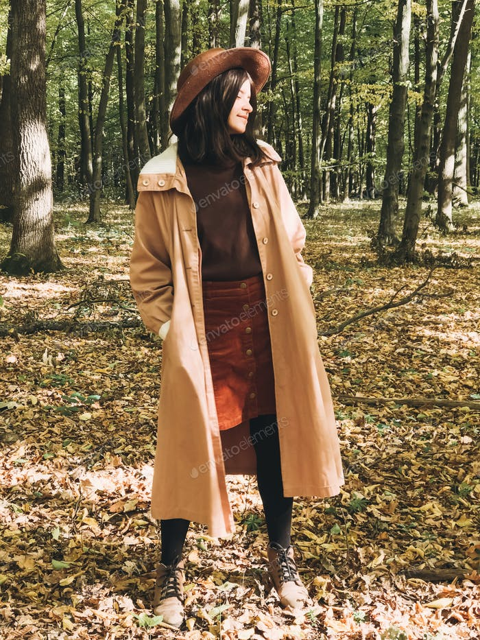 Hipster woman in hat and coat traveling in autumn sunny forest